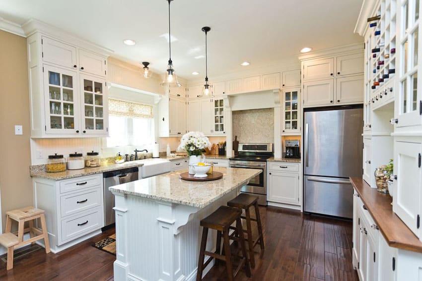 Kitchen with white cabinets, breakfast bar, dark mazama hardwood floors and cafe crema granite counters
