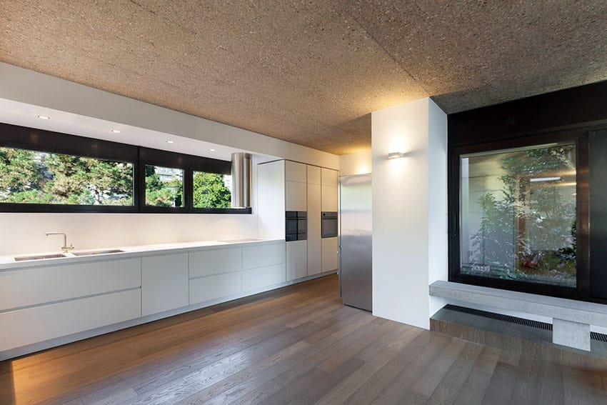 Modern galley kitchen with white cabinets, concrete ceilings, wood flooring and garden atrium views