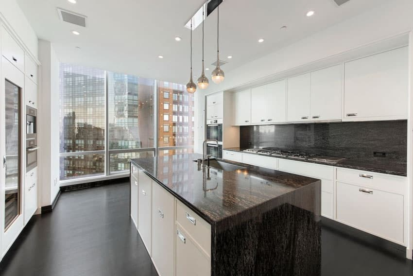 Modern kitchen with white cabinets and apartment city views