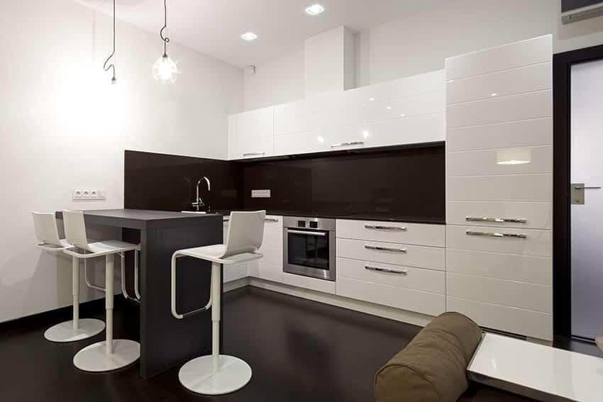 Modern white kitchen with small breakfast bar peninsula and brown glass backsplash