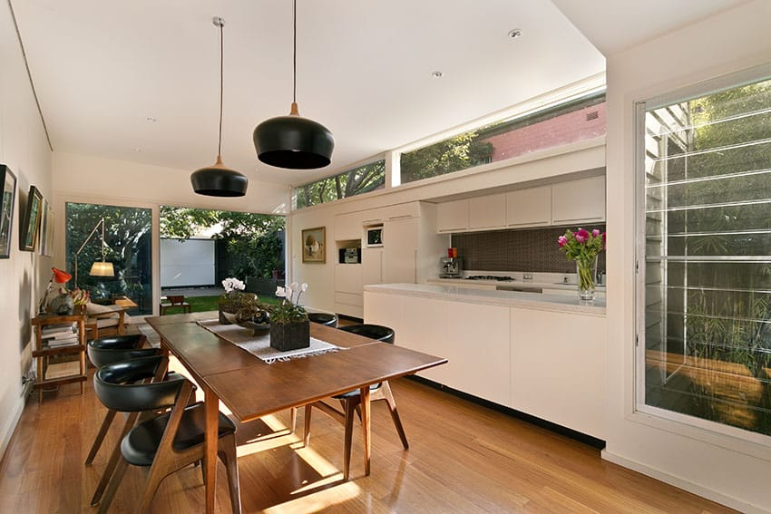White modern kitchen with peninsula wood dining table and wood flooring