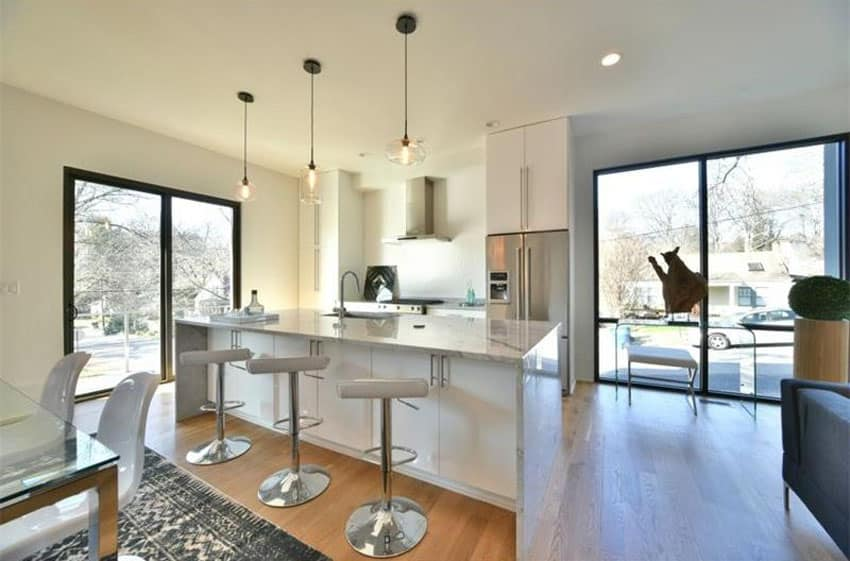White modern kitchen with breakfast bar, chrome adjustable bar stools and round pendant lights