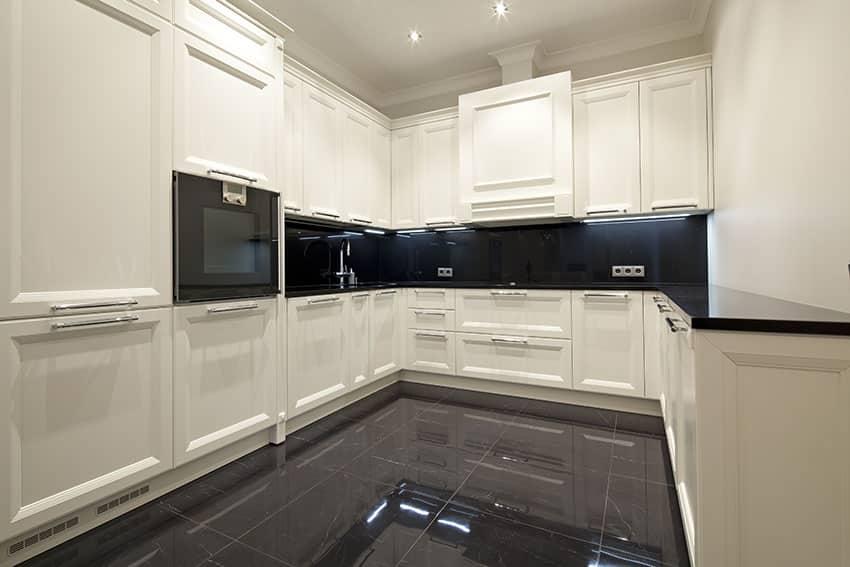 White modern u shaped kitchen with black counter and backsplash