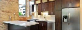 contemporary-kitchen-with-dark-brown-cabinets-white-quartz-counters-and-exposed-brick-walls