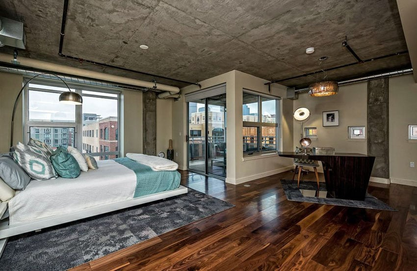 Contemporary loft bedroom with balcony, wood floors, concrete ceiling and exposed duct work
