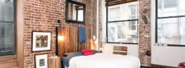 rustic-brick-loft-bedroom-with-wood-flooring-and-exposed-beam-ceiling