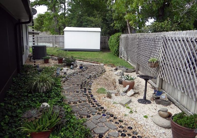 Backyard with walkway of stone pavers and glass bottles
