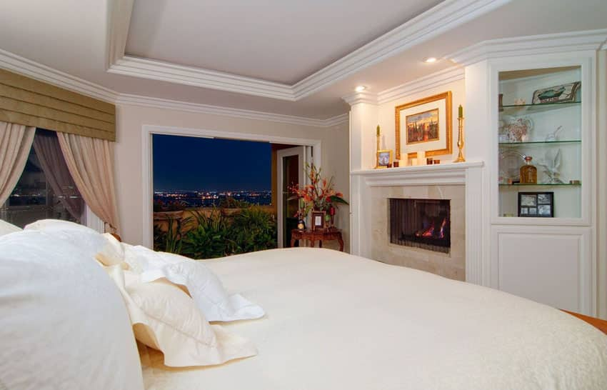 Bedroom with fireplace and city view