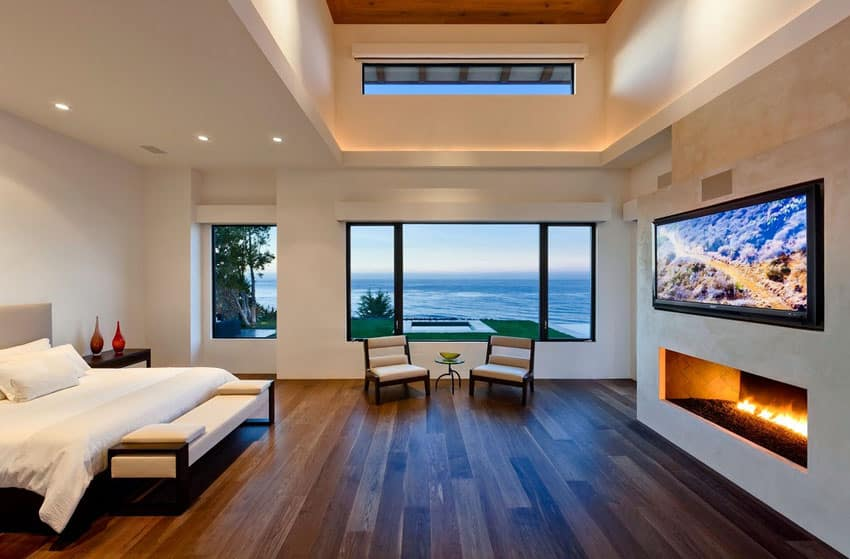 Contemporary bedroom with fireplace and water view