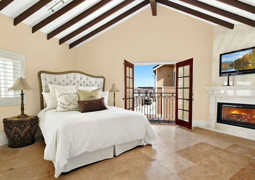 Mediterranean master bedroom with fireplace, arched ceiling and outdoor balcony views