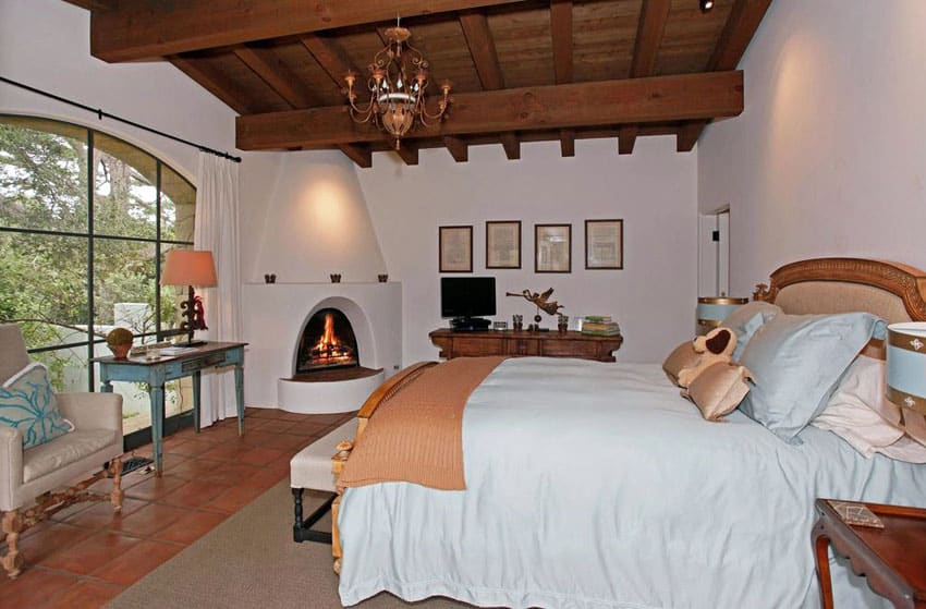 Mediterranean master bedroom with fireplace and terracotta tile floors
