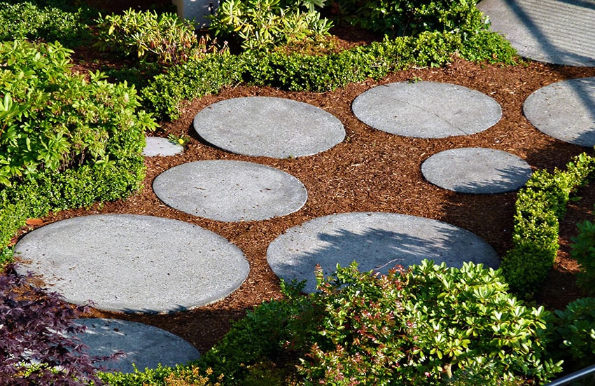 Round garden pavers surrounded by bark and bushes
