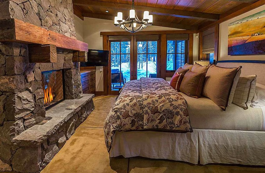 Rustic craftsman style bedroom with rough stone fireplace and forest views