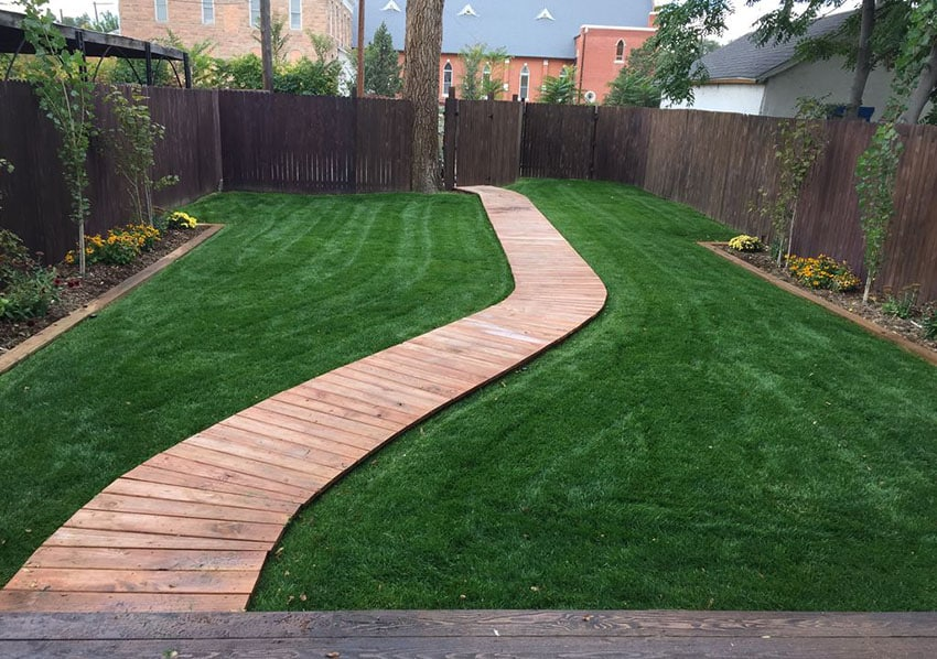 Wood deck walkway through backyard lawn