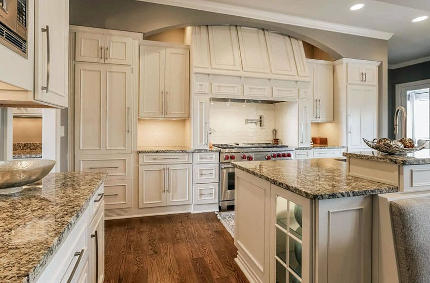 Kitchen With White Cabinets And Bianco Antico Granite