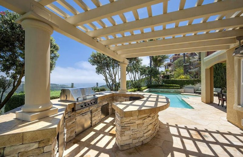 style patio with outdoor kitchen and covered pergola