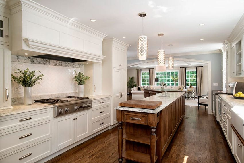 Beautiful kitchen with white cabinets and narrow center island with sink and small butchers block