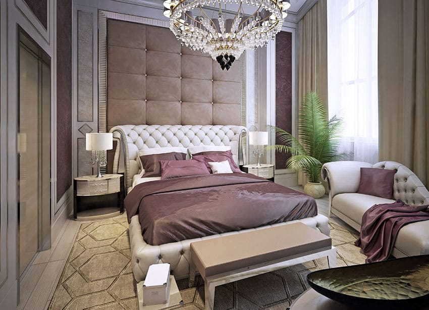 Beautifully decorated bedroom with tufted bed, matching loveseat, accent wall and chandelier
