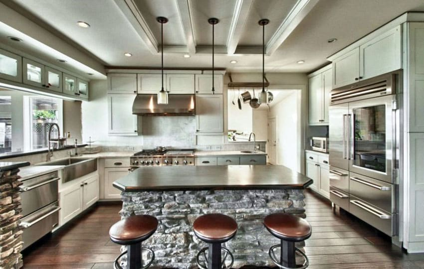 Gourmet chefs kitchen with high end appliances and breakfast bar with bar stools