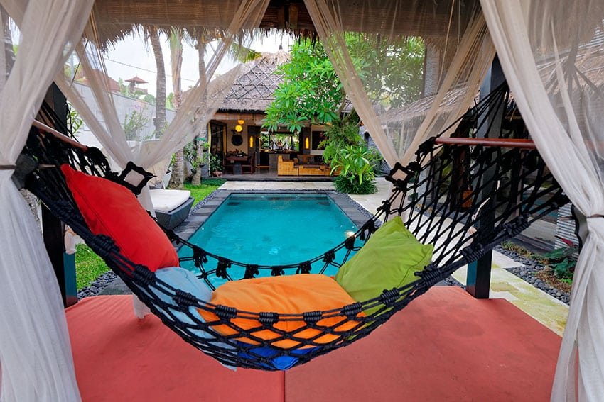 Inside a pool cabana with a hammock and sheer curtains