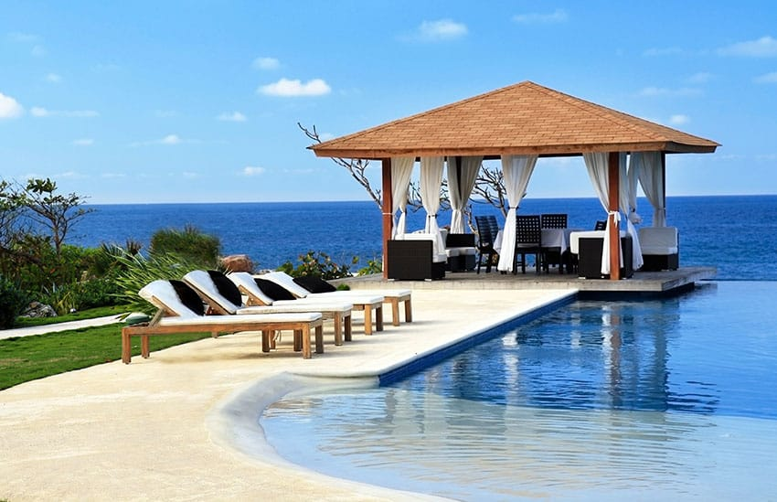 Pavilion with outdoor furniture next to swimming pool with oceanviews