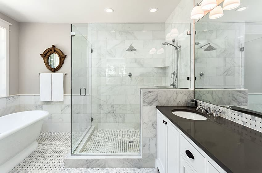 Luxury white marble bathroom with large glass walk in shower, white vanity with black countertops