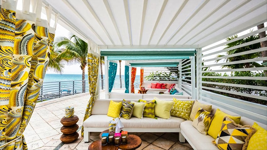 Oceanfront cabana with colorful decor and curtains