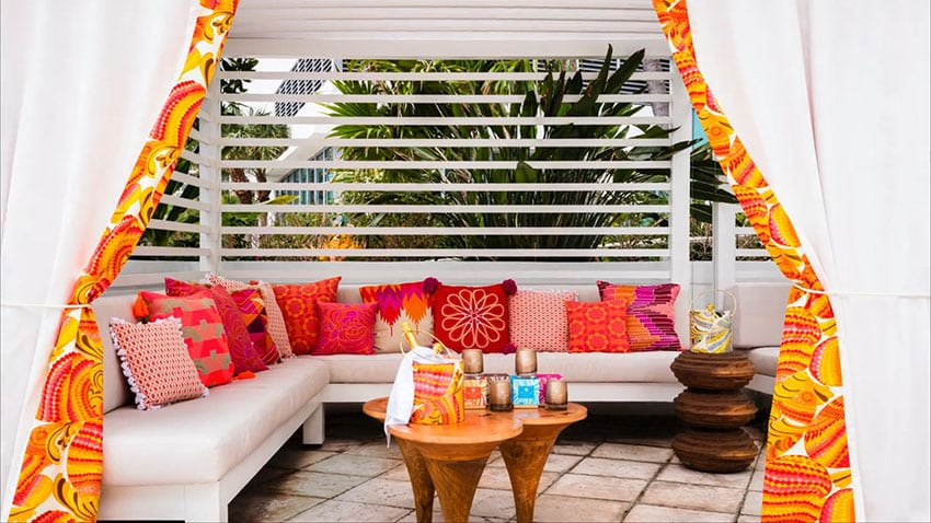 Pool cabana with bright pillows and orange curtains