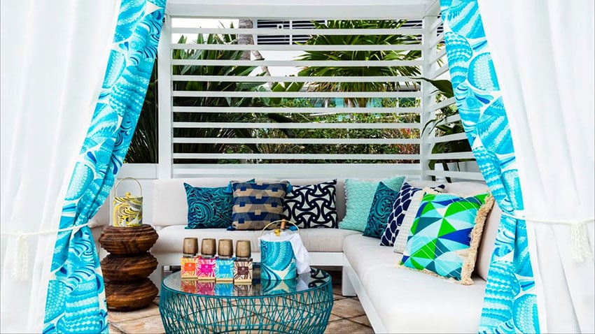 Pool cabana with colorful pillows and canopy curtains