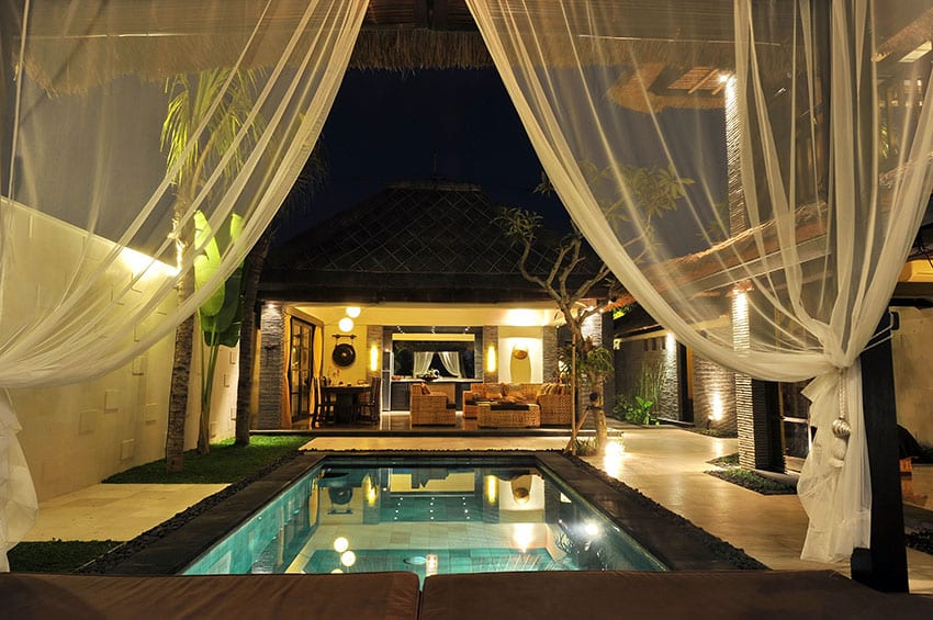 Pool cabana with daybed and sheer curtains