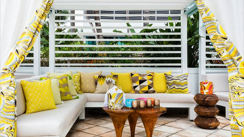 Pool cabana with yellow cushions and curtains