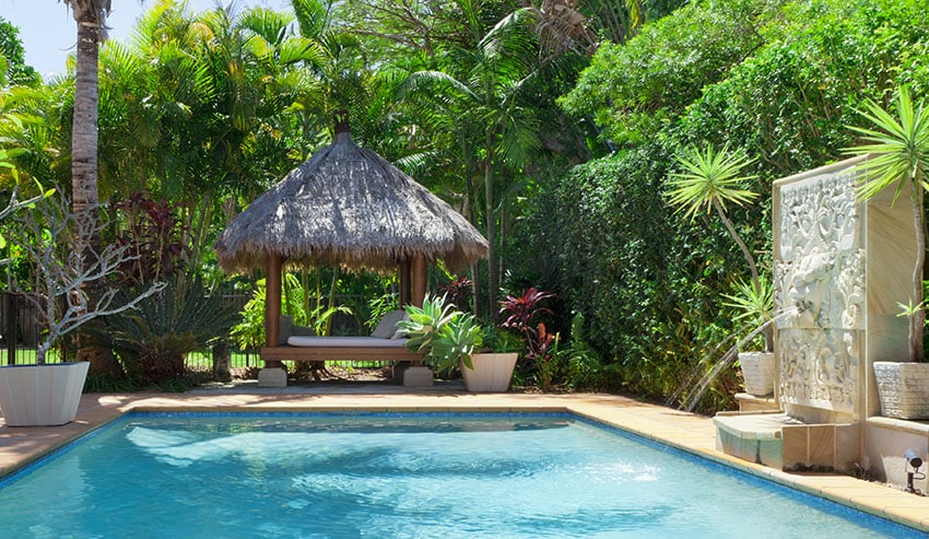 Backyard with swimming pool and thatched cabana with daybed