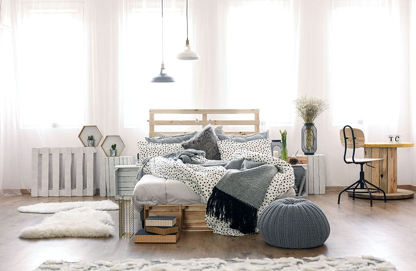 Stylish pallet headboard in bedroom with reclaimed spool table and pallet end tables
