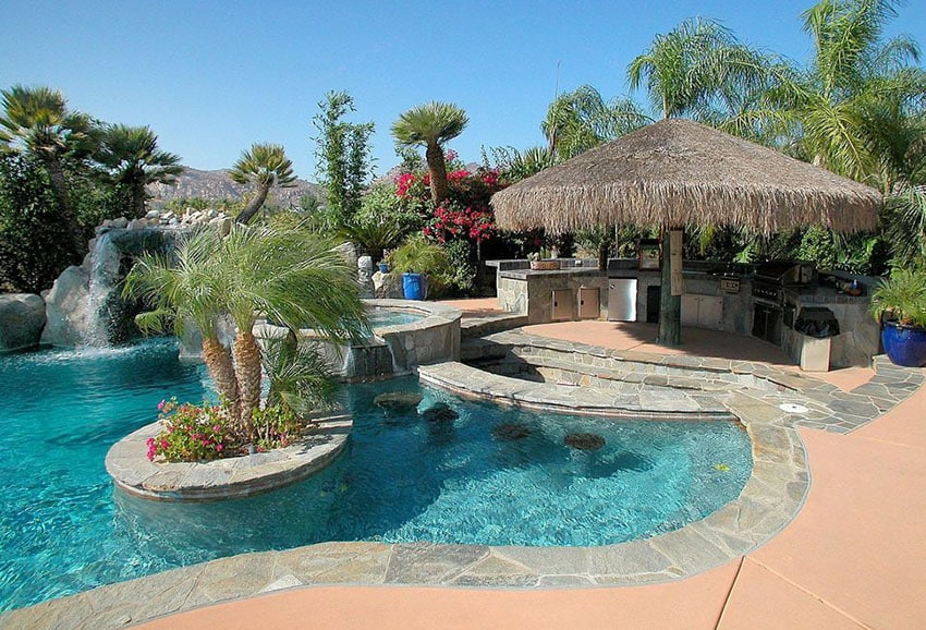 Tropical swimming pool with thatched palapa and outdoor kitchen