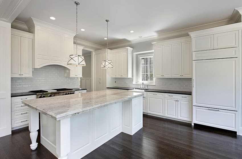 White kitchen with white subway tiles, large island, granite counters and drum pendant lights