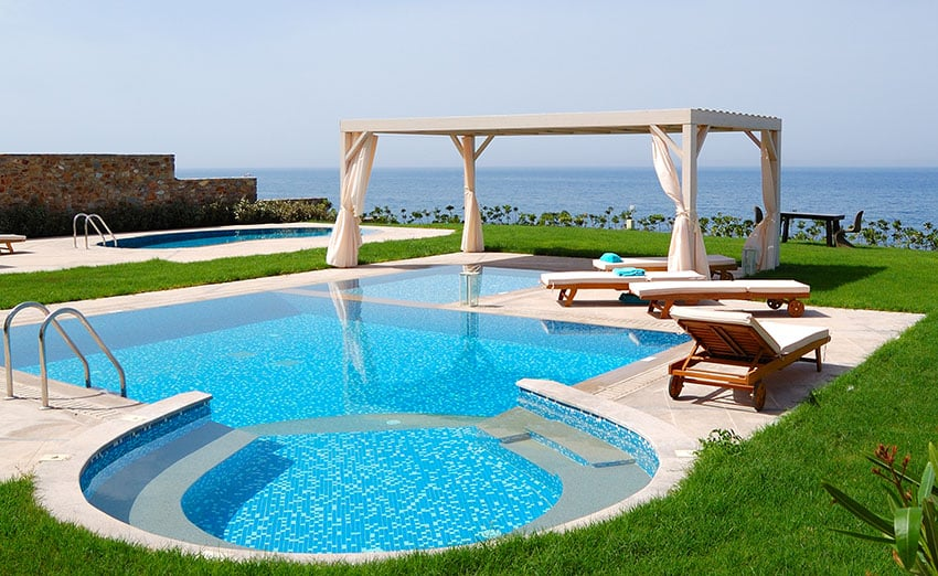 Swimming pool with jacuzzi at the beach of modern luxury villa