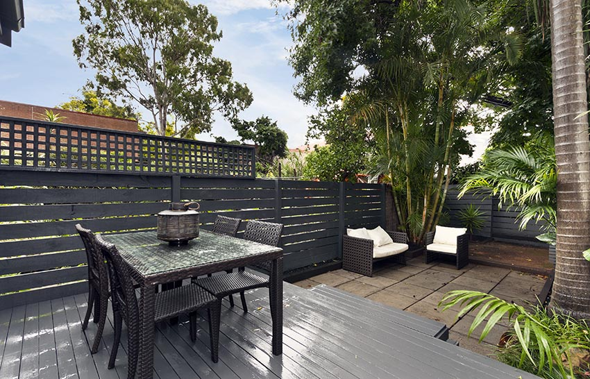 Backyard deck with dark brown painted fence with lattice top