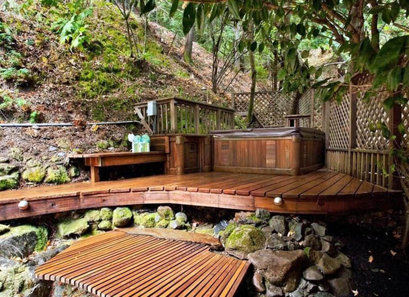 Backyard deck with elevated hot tub and lattice fence