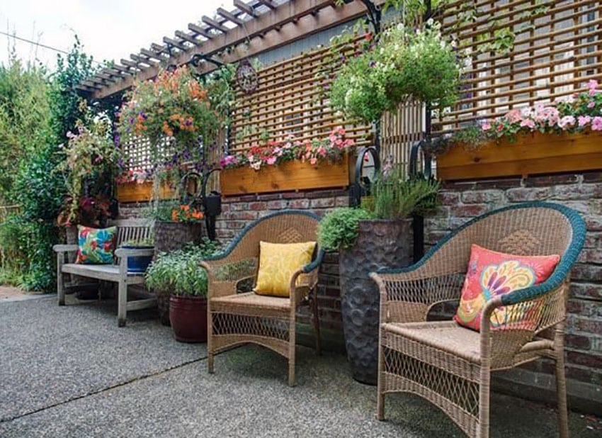 Backyard patio with wood flower boxes and narrow pergola