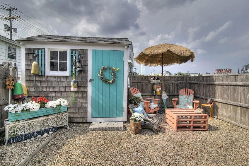 Backyard with gravel patio and flower box next to wood shingle shed