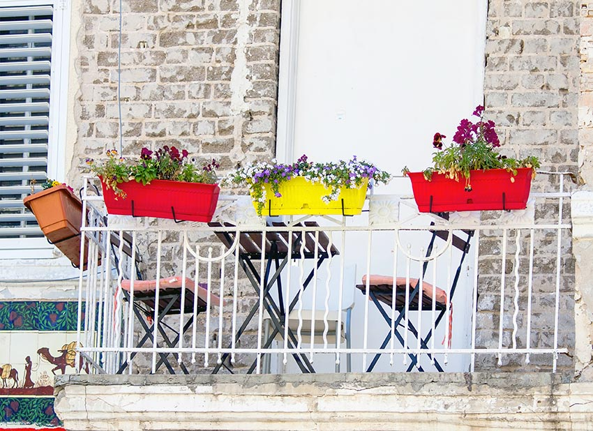 Colorful balcony flower boxes on metal railing brick house