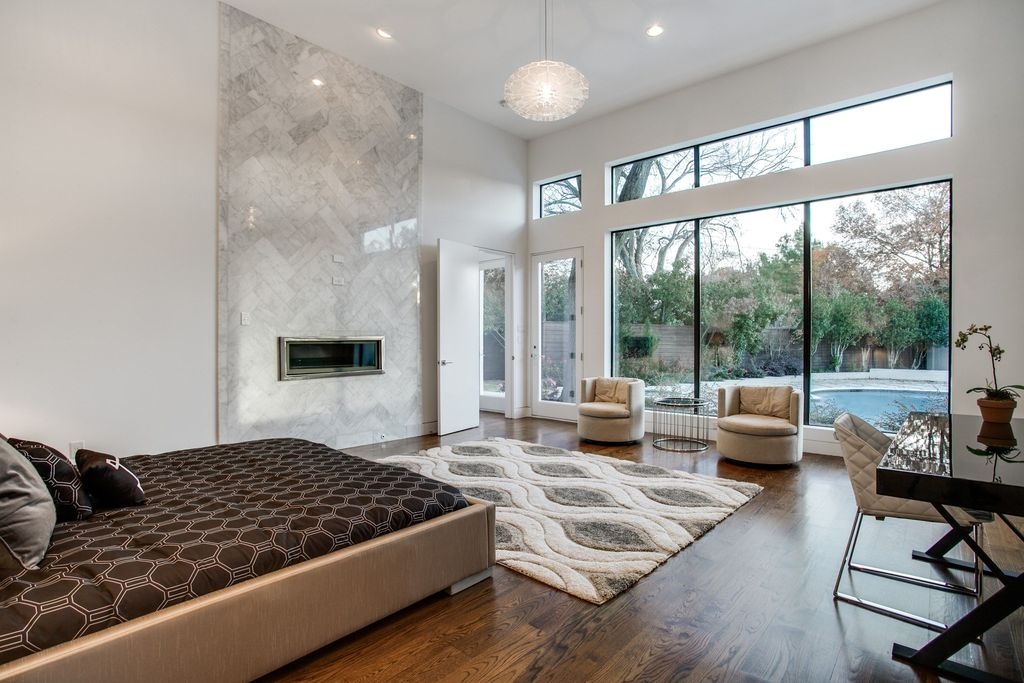 Contemporary bedroom with queen size bed, wood floors, round pendant light and backyard views