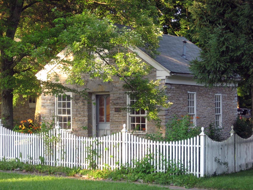 Cottage with white picket fence with curved design and decorative posts