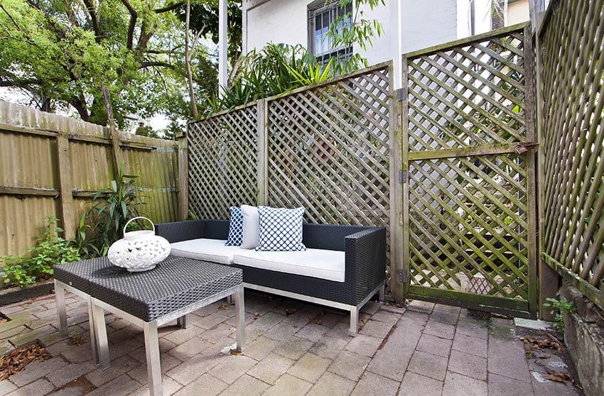 Cozy backyard patio with wood lattice fence
