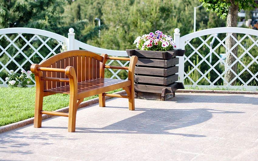 Decorative short white lattice fence next to bench sitting area