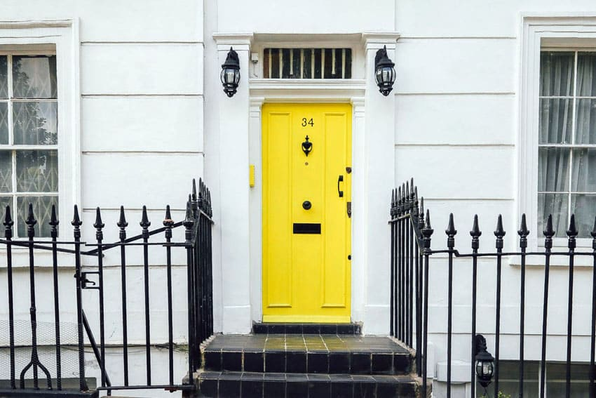 Metal picket fence in front of house with yellow door
