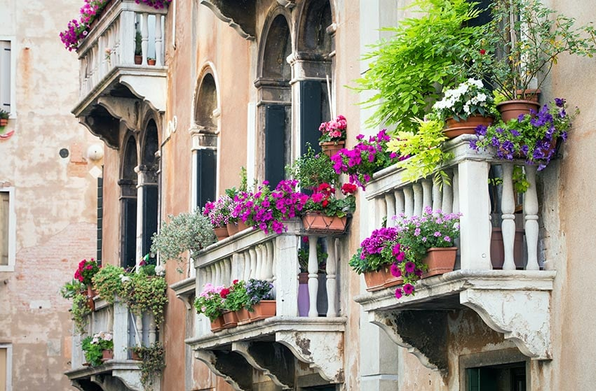 Old rustic building with decorative balcony with flower boxes