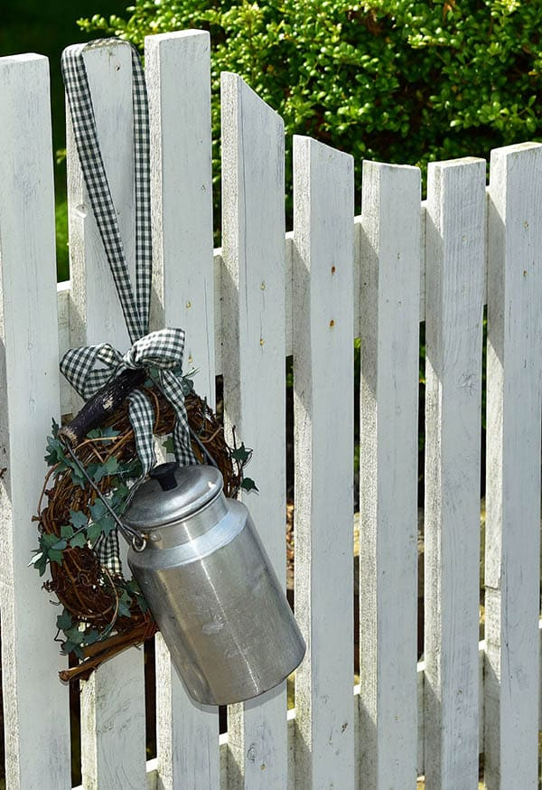 Picket fence with wreath and milk can decor