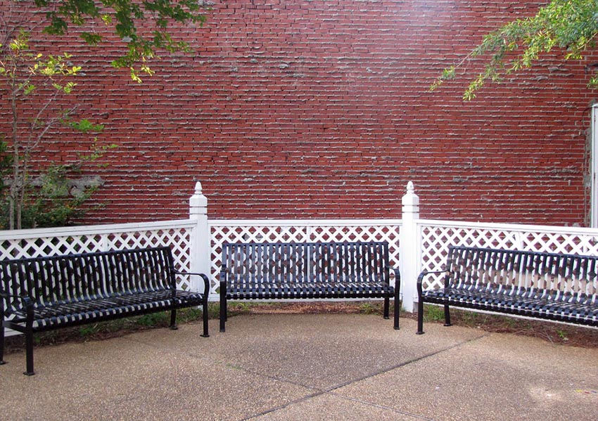 Small white lattice fence with posts and park benches