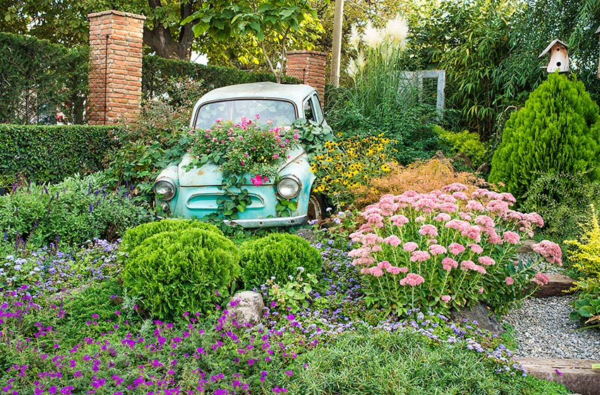 Vintage old car as flower box in garden